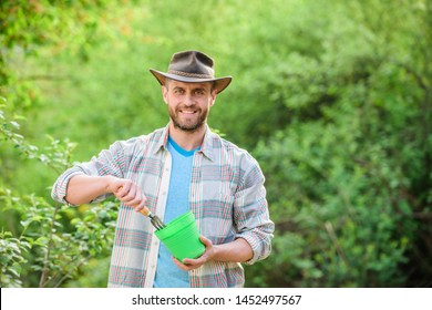 satisfied farmer hold garden rake and flower pot. muscular ranch man in cowboy hat. farming and agriculture. Garden tools. Eco farm worker. Harvest. happy earth day. Eco living. Flowers presentation.