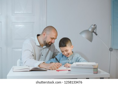 Satisfied father and son work together on school homework or homeschooling.
