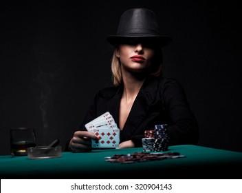 Satisfied female gambler shows royal flush in her hand. Dark color Intensity.