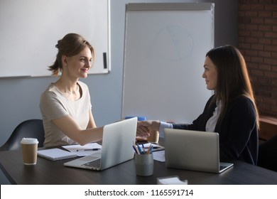 Satisfied female partners shaking hands after successful business negotiations in company office, happy businesswomen handshaking closing deal during boardroom meeting, colleagues making agreement