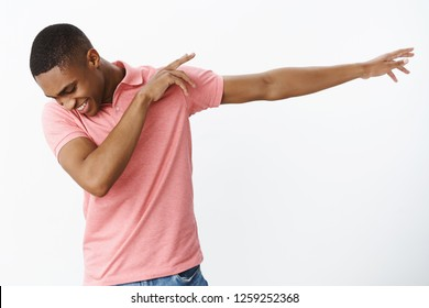 Satisfied happy and charismatic joyful african american young guy making dab pulling hands right tilting, looking down with broad happy smile dancing, having fun over gray background