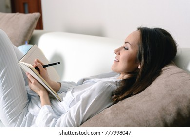 Satisfied and happy smiling girl lying on the sofa in the room and writes a journal of your dreams, plans, goals, experiences, ideas, lived emotions and feelings.