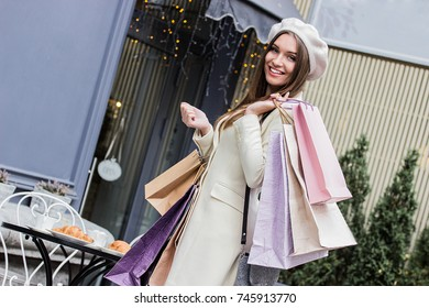 Satisfied with her shopping day. Low-angle view of beautiful french woman in beret looking to camera and smiling while posing with shopping bags against french cafe. Shopaholic woman.