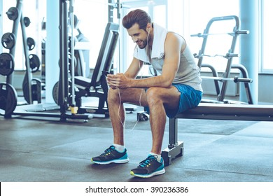 Satisfied with his work out. Handsome young men in headphones using his smart phone with smile while sitting at gym