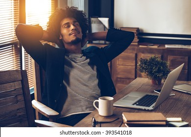 Satisfied with his work. Young handsome African man keeping hands behind his head and looking satisfied while sitting at his working place