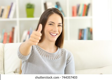 Satisfied home owner looking at you with thumbs up sitting on a couch at home
