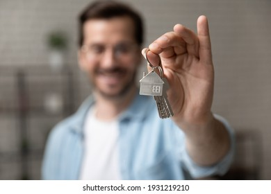 Satisfied homeowner. Blurred portrait of happy young man buyer renter of new modern home apartment holding key demonstrating wellbeing wealth celebrate achievement. Focus on hand with keys of dwelling