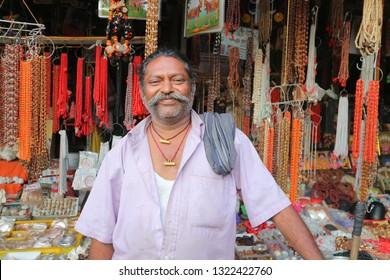 Satisfied Indian souvenir and bead merchant looking at the camera. India, Tirumala, Papavinashanam, February 24, 2019.