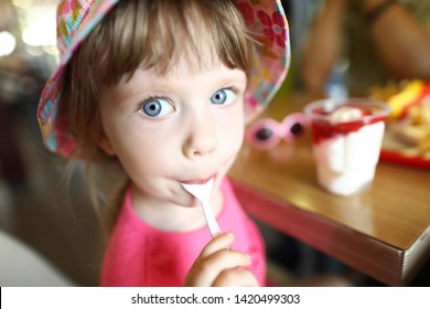 Satisfied little child licks spoon with ice cream on cafe background