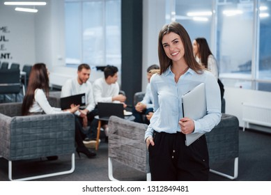 Satisfied look. Portrait of young girl stands in the office with employees at background.