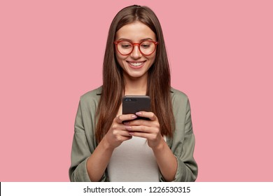 Satisfied lovely woman holds modern cell phone, texts with friend online in chat, dressed in stylish clothes, poses against pink wall, connected to high speed internet. Shot of teenager with device