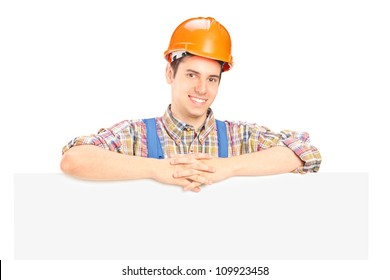 Satisfied male construction worker standing behind white panel