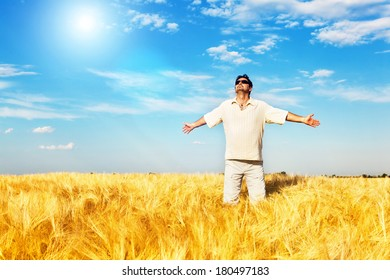 Satisfied man with arms outstretched standing in the wheat field, flare light.Copy space