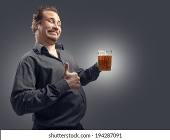 Satisfied man with beer on a dark background. Studio photography.