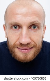 Satisfied man with a ginger beard looks in the frame, close-up, white background