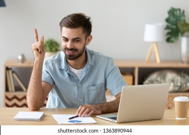 Satisfied man with raised hand thinking about good creative interesting idea, happy student found new solution for research work, freelancer or businessman sitting in office or at home with laptop
