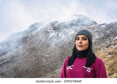 A satisfied Mexican woman looking at the camera on the summit of the Iztaccihautl Volcano in Mexic