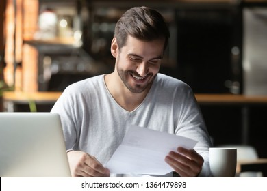 Satisfied millennial businessman sitting in cafe near computer holding paper reading letter feels happy overjoyed concept of getting notification bank loan approval, credit business, deal confirmation
