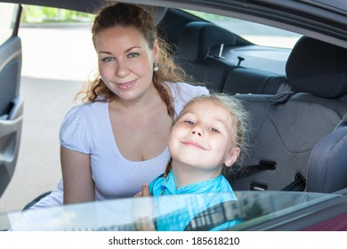 Satisfied mother and little child fastened in safety car seat