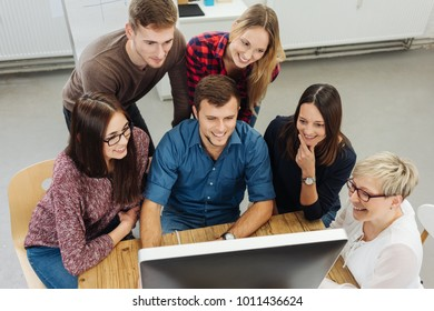 Satisfied motivated young business team sitting grouped around a desktop monitor smiling at a successful outcome