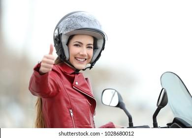Satisfied motorbiker gesturing thumbs up on her motorcycle outdoors
