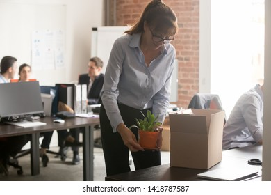 Satisfied newcomer middle aged female company worker in glasses standing in shared coworking office unpacking cardboard box with personal belongings at new workplace having first working day concept
