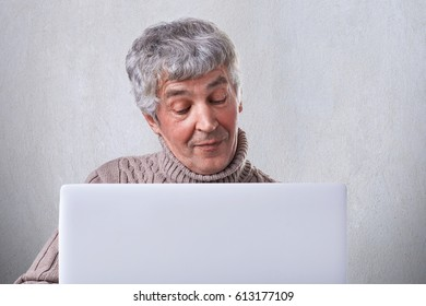 A satisfied old male having conversation online on his laptop while siting at home. An attractive mature man browsing internet using laptop computer isolated over white background.