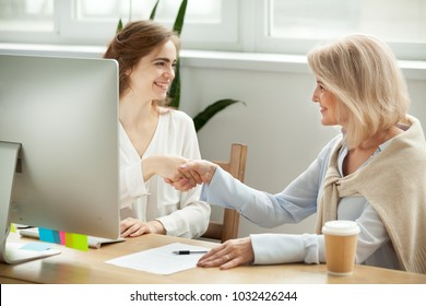 Satisfied older woman and young manager handshaking after signing contract in office, happy senior female client and smiling insurance broker or financial advisor making deal agreement shaking hands