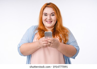 Satisfied plus size woman using mobile phone isolated over white background
