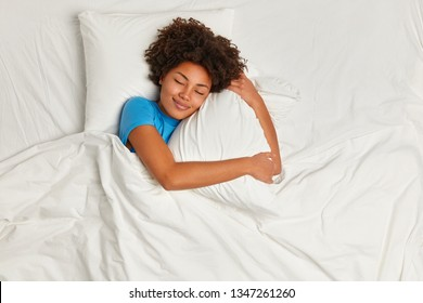 Satisfied pretty Afro American young woman has peaceful sleep, lies in bed on comfortable pillow, sees pleasant dreams, has gentle smile, enjoys softness of bedclothes, being under white blanket