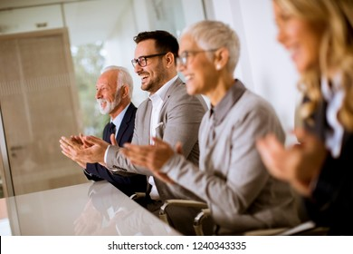 Satisfied proud business team clapping hands while sitting in row at office
