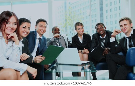 Satisfied proud business team looking at camera and smiling in office.