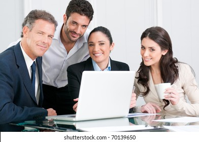 Satisfied proud businss team looking at camera and smiling in office