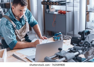 Satisfied self-employed engineer working at desk with laptop, metal parts and gloves