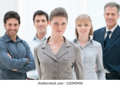 Satisfied smiling business woman standing with her colleagues at modern office
