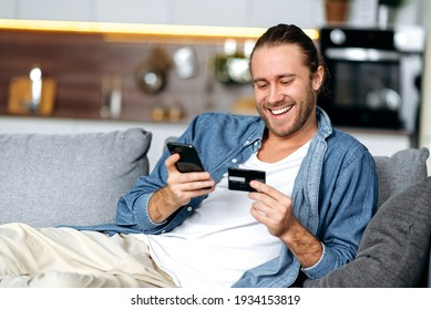 A satisfied smiling caucasian guy, in casual stylish clothes, sits on the couch at home, holds a phone and a credit card in his hands, pays for online purchases, enters a card number, online shopping