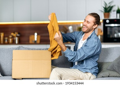 A satisfied smiling guy unpacks his long awaited package, examines the clothes that he bought online, is happy with the purchase, sits at home on the sofa in the living room. Online shopping concept