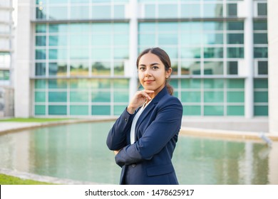 Satisfied successful business leader posing outside. Beautiful Latin woman wearing formal suit, standing near office building, touching chin and looking at camera. Young business woman concept