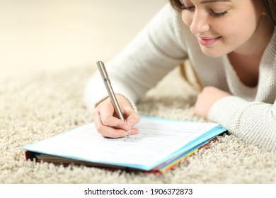Satisfied teen filling form lying on a carpet at home