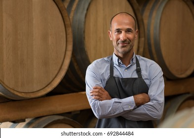 Satisfied winemaker in cellar with folded hand. Happy man standing in his warehouse and looking at camera. Smiling professional man standing in wine cellar with wine wooden barrels in background.