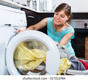 Satisfied woman enjoying clean clothes without stains after laundry