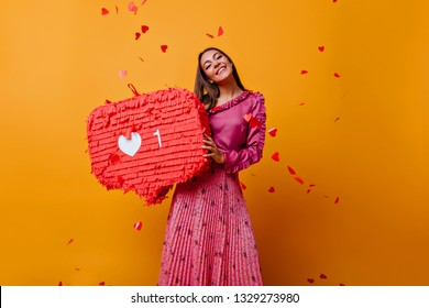 Satisfied woman in pink outfit laughing in studio. Adorable caucasian girl in long skirt standing on yellow background.