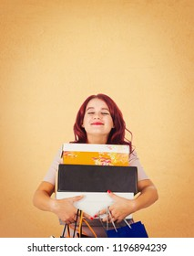 Satisfied woman shopaholic holding a stack of boxes and paper bags dreaming eyes closed isolated over orange background with copy space above head.