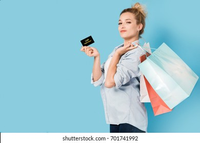 Satisfied woman with shopping bags and VIP card in hand