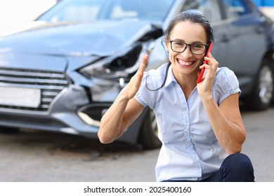Satisfied woman talking on mobile phone near wrecked car
