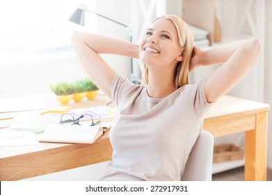 Satisfied with the work done. Beautiful young woman holding hands behind head and smiling while sitting at her working place in office