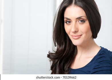 Satisfied young beautiful lady looking at camera and smiling