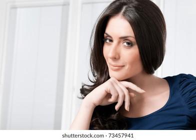 Satisfied young beautiful woman looking at camera at home
