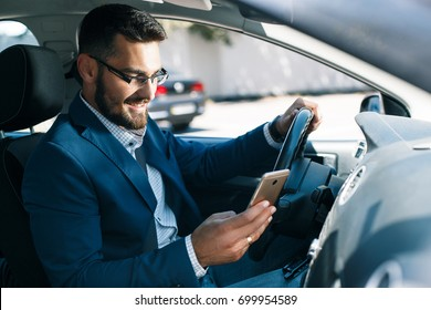 Satisfied young business man with phone in car
