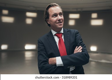 Satisfied young businessman with red tie in empty room.